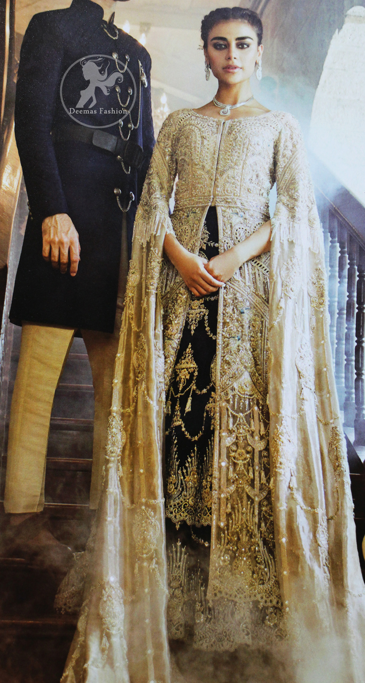 An ivory front open tissue shirt with heavy embroidery decorated with dull golden and champagne kora, dabka, tilla, naqshi, sequins and swarovski. It is further allured with cutwork and floral embroidery. Its umbrella sleeves is embellished with delicate zari work. Its black inner shirt is also embroidered. This outfit is artistically coordinated with black chiffon sharara which is allured with floral embroidery. This outfit is fully scalloped and enhanced by a thick floral embellished pattern. Dress comes with ivory dupatta which has finished edges and having sprinkled sequins pattern all over it.