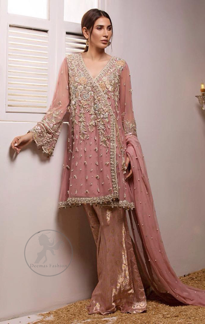 This outstanding copper rust angrakha meticulously highlighted with dull golden, tea pink and silver shaded kora, dabka , tilla, sequins and pearls. This dress is beautifully adorned with floral embroidery. It is decorated with small and large sized floral motifs. It is also embelished with beautiful tassels which adds to the look.It comes with brocade gharara pants. It is artistically coordinated with chiffon dupatta having sprinkled sequins all over it.