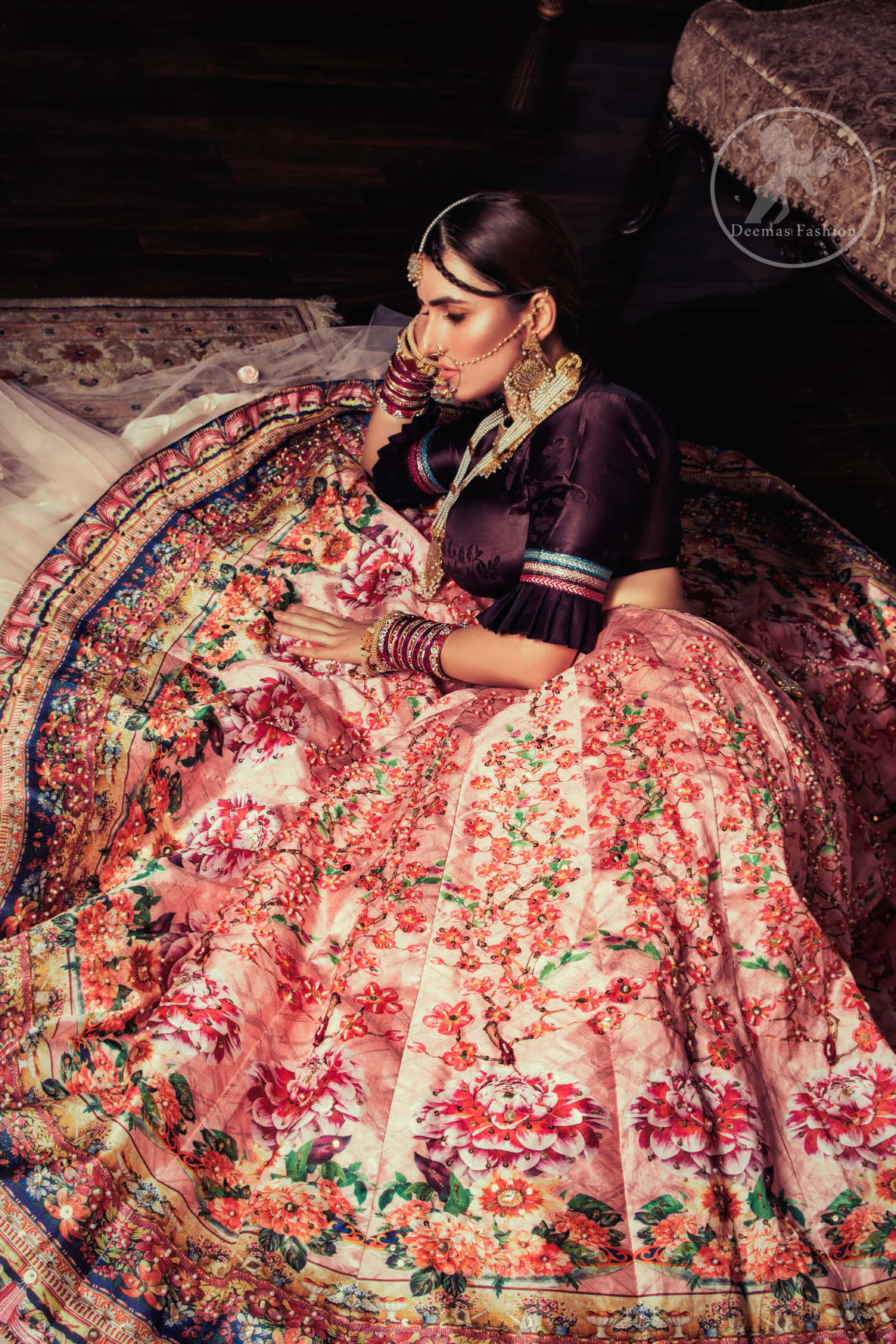 This outfit is a timeless beauty. Dark purple self-printed blouse is decorated with applique. The raw silk classic lehenga is adorned with digital print. Its floral print is further decorated with swarovski, tilla, kora dabka . Its beautiful printed border adds to the look. This outfit is beautifully coordinated with peach pink dupatta with heavy embroidered borders.
