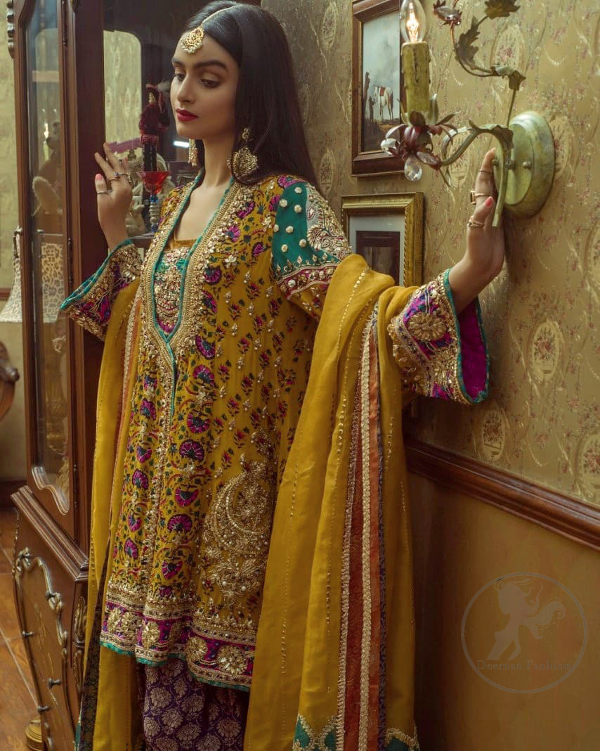 This outstanding angrakha shirt embellished with floral thread embroidery. It is allured with resham, kora dabka, tilla and pearls. Sleeves are decorated with gotta lace and floral embroidery. Embroidered applique on hemline adds to the look. It is beautifully paired up with magenta sharara with gotta criss cross patterns. It comes with chiffon goldenrod dupatta embellished with pea green applique.