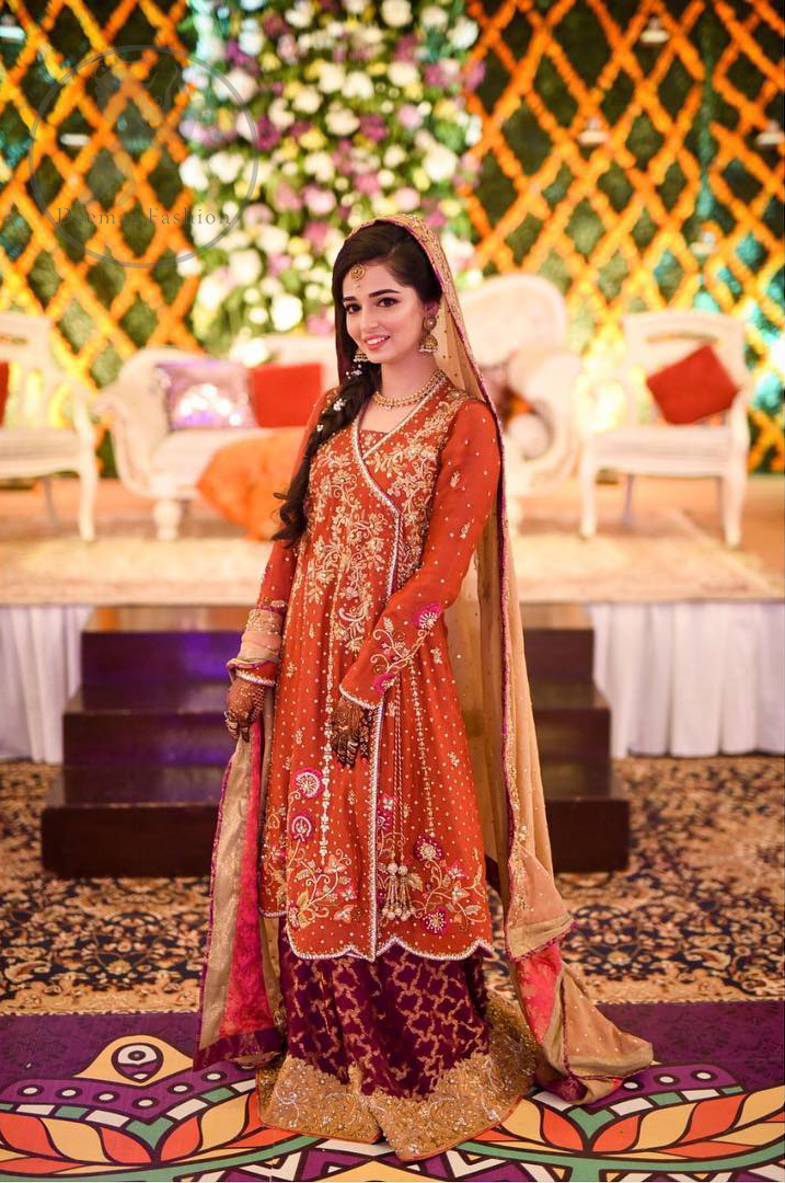 This outstanding outfit is fully embellished with embroidery. It is allured with resham, kora dabka, tilla and pearls. Sleeves are decorated with floral embroidery. Its neckline and hemline is adorned with floral motifs.It comes with embellished sharara which has small sized sprinkled floral motifs at the bottom. This Outfit is beautifully coordinated with dull yellow dupatta with heavy embroidered borders.