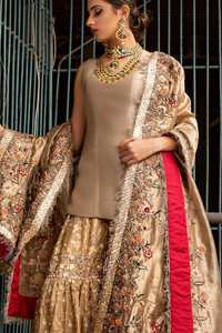 Ivory plain shirt is paired up with golden traditional gharara done with floral motifs all over. It is beautifully matched with golden dupatta with colorful embellished motifs at both lengths and lace border finished around dupatta.