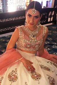 The blouse is beautifully embellished with cutwork embroidery enhanced with silver gold kora dabka, kundan and sequins work. It is paired up with ivory lehenga with colorful pattern embellishment ornamented with kora dabka, and colorful thread embroidery. It comprises with peach dupatta sprinkled sequins all over.