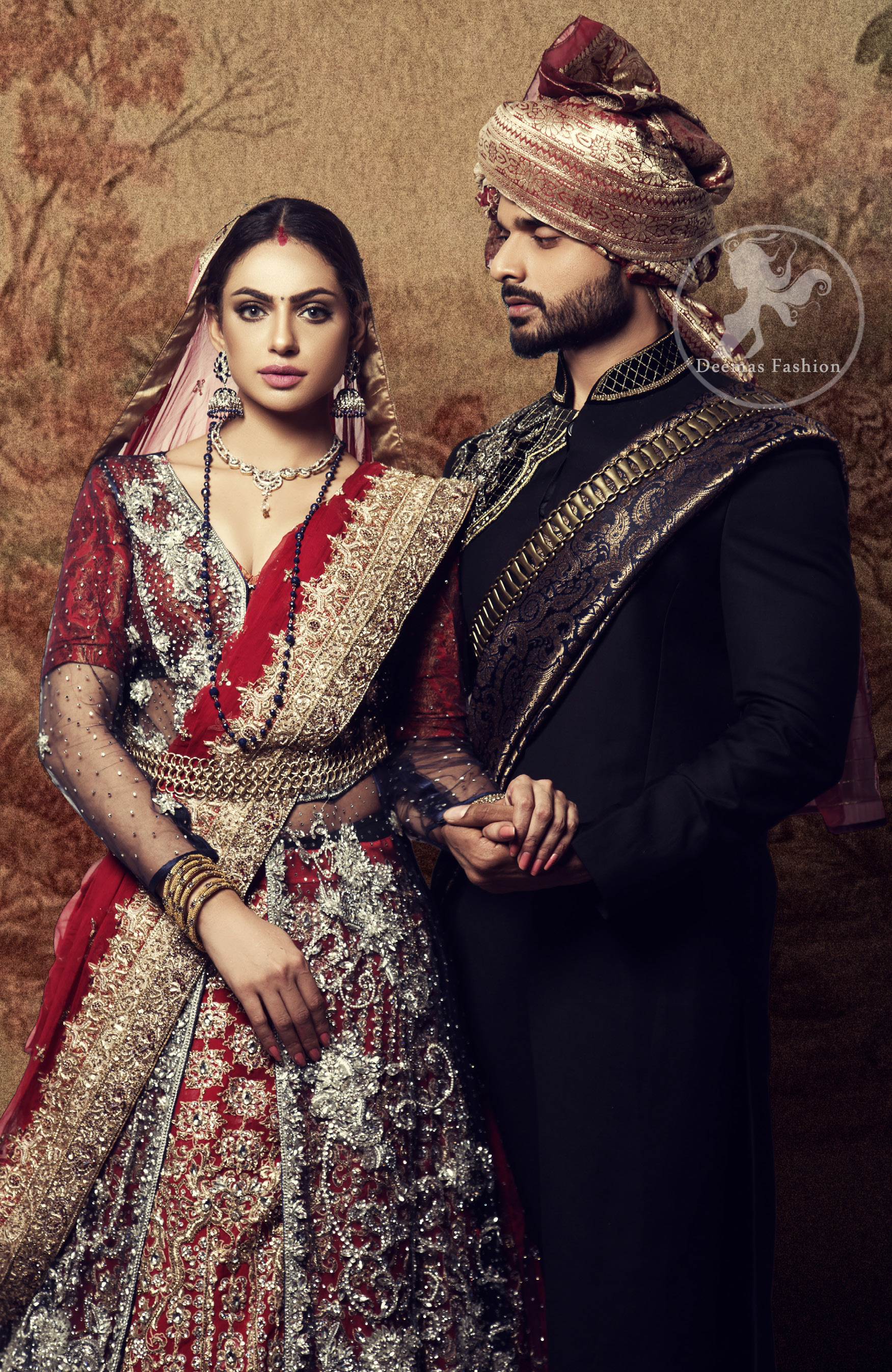 This dress is timeless beauty. Black floor length net paneled gown is beautifully embellished with silver kora dabka, tilla, pearls and sprinkled sequins all over. It comprises with maroon blouse and skirt. The skirt is ornamented with floral motifs done with silver gold kora dabka, tilla, kundan and sequins work. This outfit is coordinated with maroon dupatta with embroidered borders on all four sides and sequins work on the ground.
