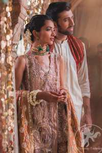 This outfit is executing heavily handcrafted art of zardozi. It is allured with kora, dabka, tilla, sequins and pearls. It comes with raw silk dupatta which is fully embellished. It comes with an exquisite high and low short shirt with thick embroidered borders to give it a regal look. This outfit is artfully coordinated with bell bottom embroidered trousers.