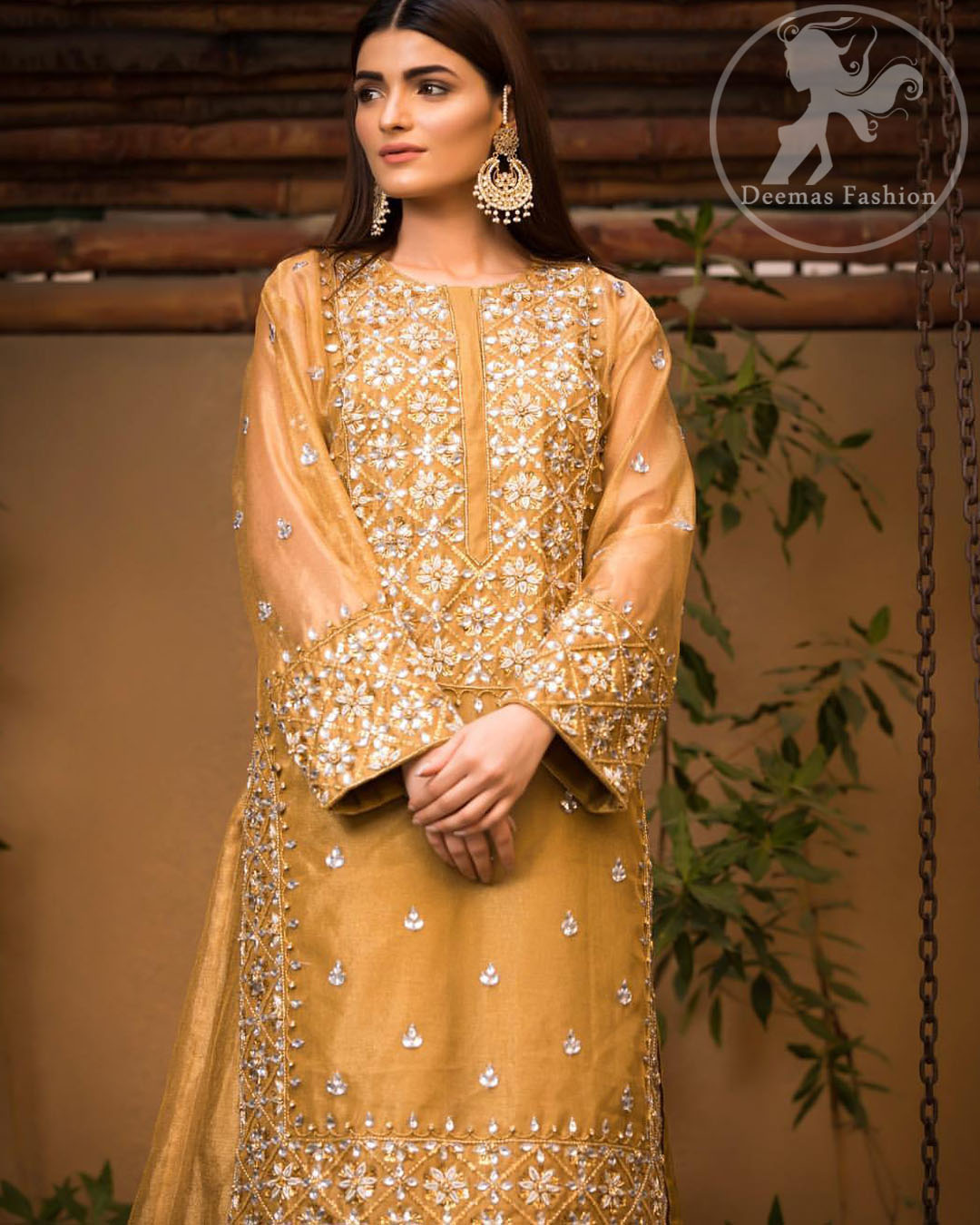This dress is allured with floral embroidery. It is further enhanced with gota, kundan, sequins and pearls. It comes with organza lehengha. It is artistically coordinated with velvet shawl, having four sided embellished scalloped border.