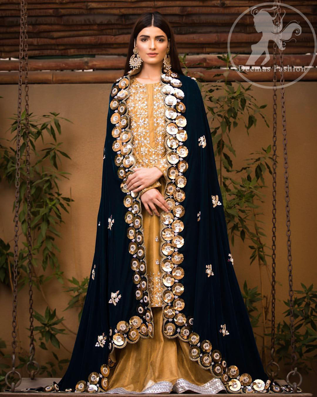 This dress is allured with floral embroidery. It is further enhanced with gota, kundan, sequins and pearls. It comes with organza sharara. It is artistically coordinated with velvet shawl which is adorned with small floral motifs, also having four sided embellished scalloped border.