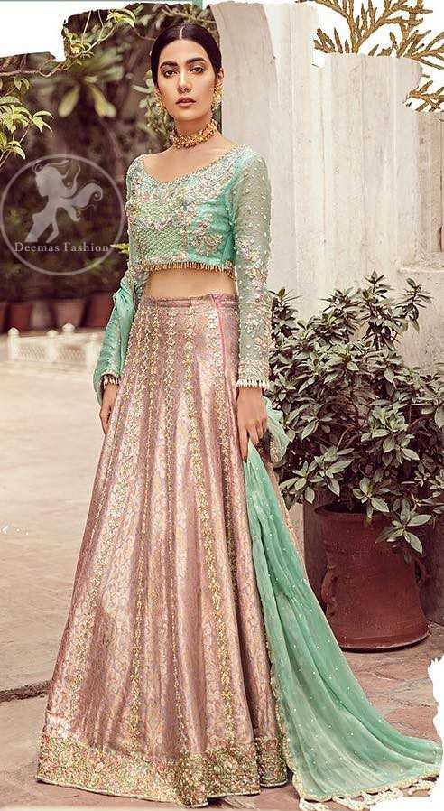 The bridal stands out due to its uniqueness and the perfect fusion of modern cut and traditional embroidery. This dress is beautifully decorated with heavy embroidery. It is highlighted with dull golden kora, dabka, tilla, sequins, pearls and thread embroidery. This outfit comes with salmon pink lehenga which is enhanced with embroidery on bottom. It is coordinated with tissue dupatta which is sprinkled with sequins all over it. It is further furnished with four sided scalloped border.