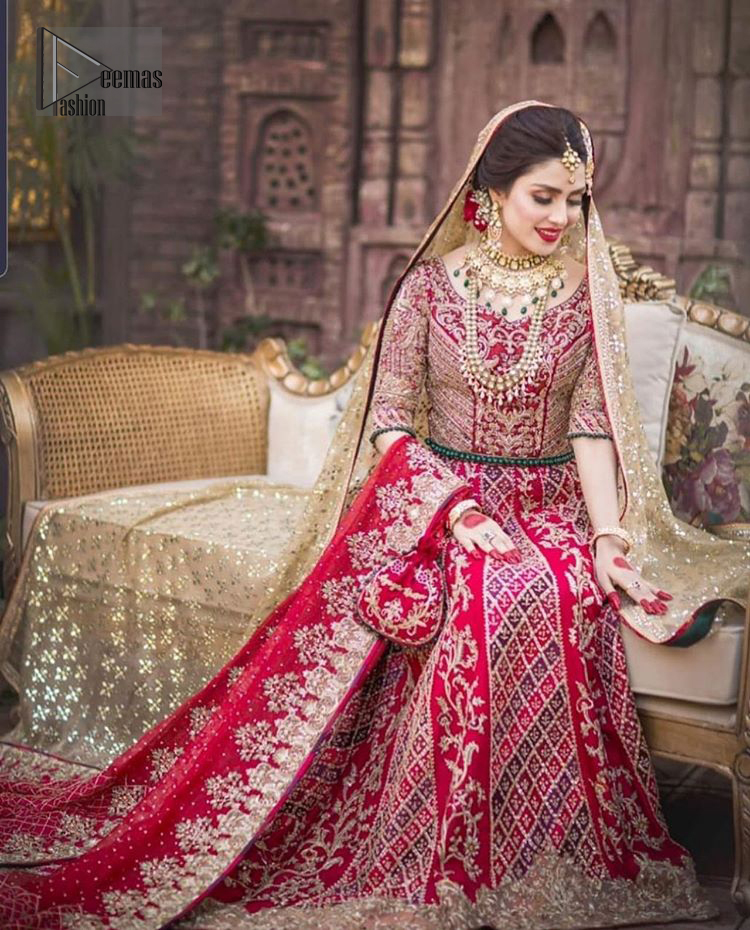 A bed of red roses translated onto a dress decorated, elaborate and flamboyant elegance. This bridal wear is perfect for your big day. The bridal stands out due to its uniqueness and the perfect fusion of modern cut and traditional embroidery. The blouse is beautifully ornamented with floral embroidery and swarovski crystals lines. Finishing with green dangling beads ball at the end. Pair it up with beautiful embroidered lehenga adorned with golden kora, dabka, tilla and sequins. Furthermore it is highlighted with geometric patterns and applique details on lehenga. It is coordinated with beautiful dupatta with thick matha patti border on two sides and intricate thin border on remaining two sides.