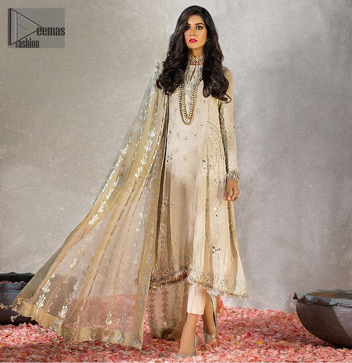 Reflecting royalty and the majestic beauty of statuesque shape and silhouette which makes the dress perfect for nikah day. This regal ivory a-line shirt is an immensely captivating traditional piece. Having full length sleeves adorned with a large floral motif in the center. The daman is furthermore highlighted with matching embellishment that instantly draws attention. It comprises with cigarette pants. Pair it up with self embroidered tissue dupatta.