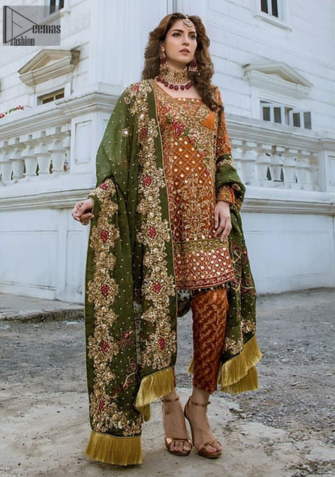 Bring out your beauty with this traditional yet modern outfit for mehndi mayon day.  Make your wardrobe more interesting with this shabby chic statement intensified with rich thread embroidery and zardosi work all over the front and geometric patterns at daman that instantly draws attention. It is highlighted with antique shaded kora, dabka, sequins and pearls. Having full length sleeves adorned with floral booties. It comprises with cigarette pants. It is coordinated with beautiful dupatta with thick embellished border on two sides and scattered sequin on the ground to convey a classic look.