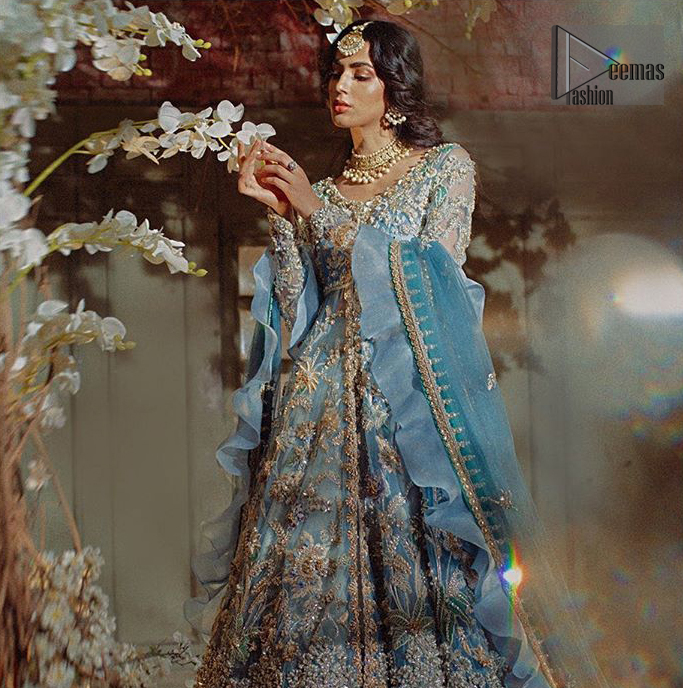 Reflecting royalty and the majestic beauty of statuesque shape and silhouette this dress is perfect for your walima and engagement function. Add some super cool twist to your look with this subtle colors in intricately embroidered frock. Capture the attention with fascinating embellishment on neckline with silver and dull golden kora, dabka, pearl and sequins. Having full length sleeves adorned with floral motifs. It comprises with ivory sharara. Thin border with floral motifs on all four sides of the dupatta which have gold tila embroidery with kora and dabka.