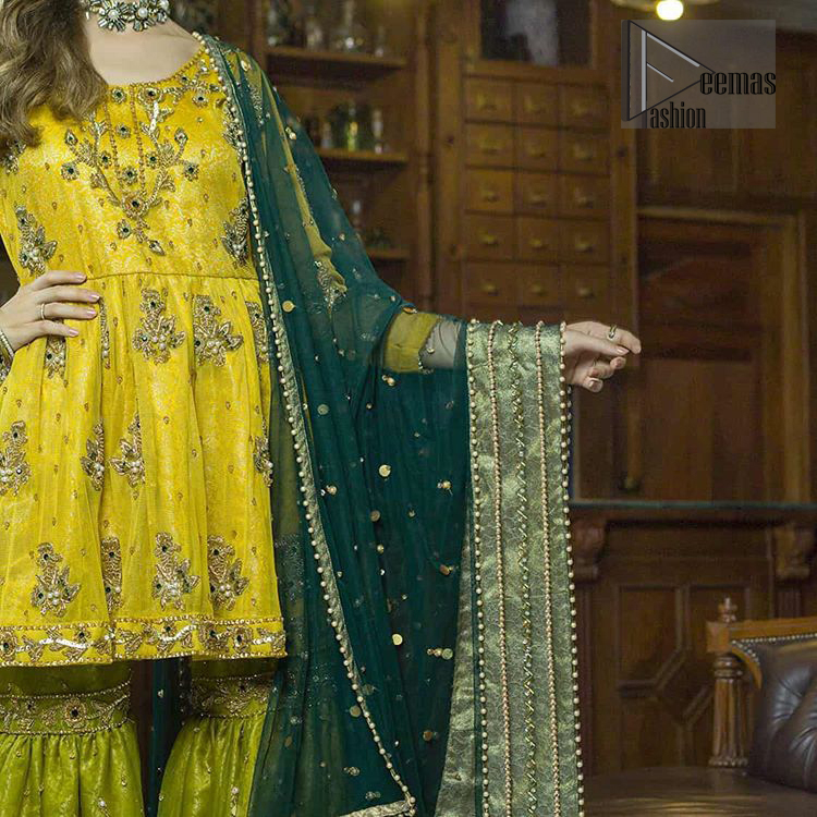 This dress is perfect for mehndi day. Delicately crafted and personifying chic elegance with an element of grandiose. This mehendi and mayun dress is beautifully sculptured with floral embroidery on neckline adorned with scattered embellished with dull golden kora, dabka, pearl and sequins work all over. Having full length sleeves adorned with motifs. It comprises with mehndi green gharara sprinkled with sequins to convey a classic style. Beautifully coordinated with bottle green dupatta with thick lace border.