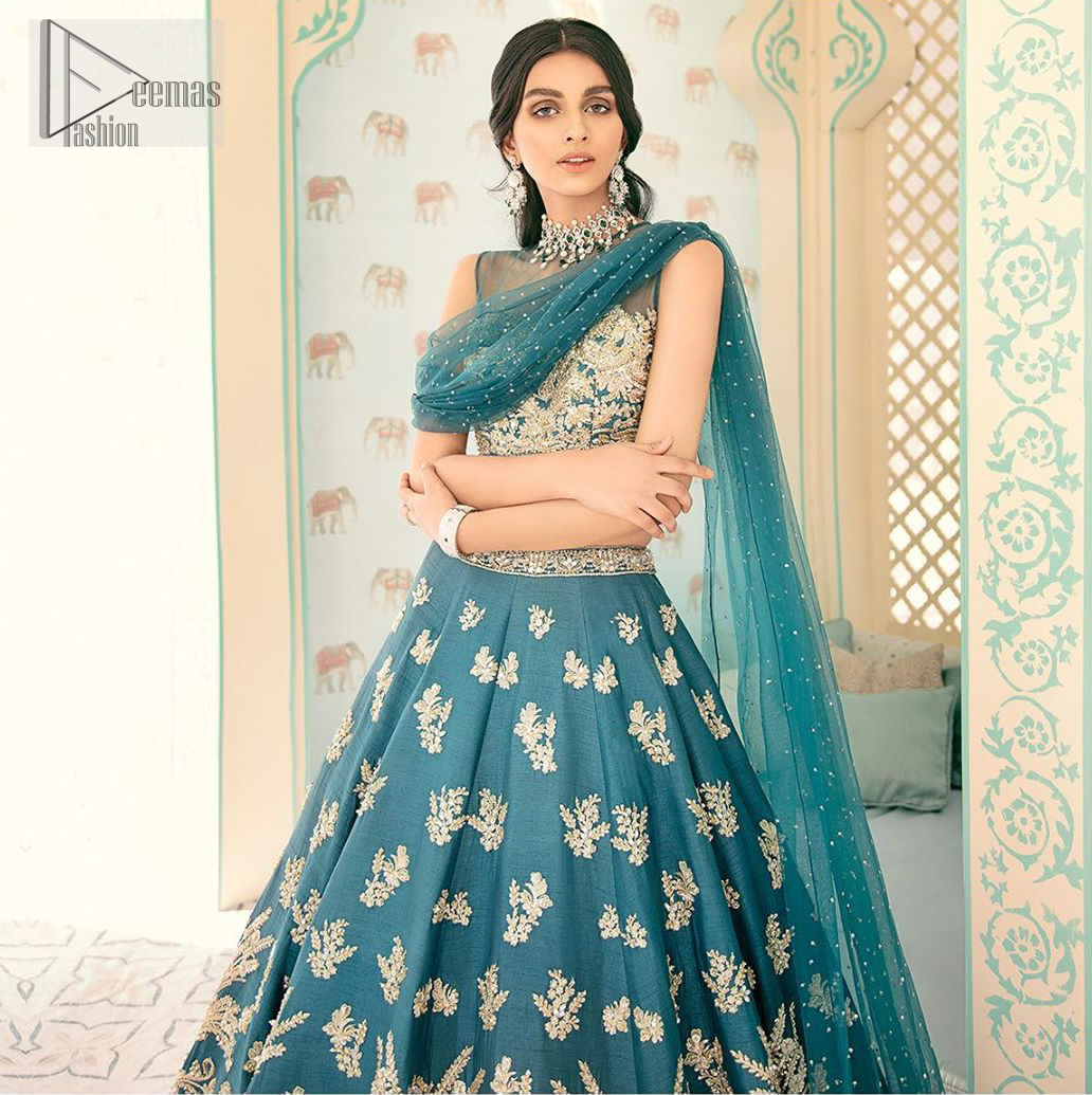 Captured in traditional silhouette. The bridal stands out due to its uniqueness and the perfect fusion of modern cut and traditional embroidery. It is highlighted with light golden kora, dabka, tilla, sequins and pearls. Blouse is enhanced with zardosi work. It comes with full embellished lehenga adorned with different size motifs and floral bunches. Style it up with net dupatta which is sprinkled with sequins all over it and embellished pallu to give it a perfect look.