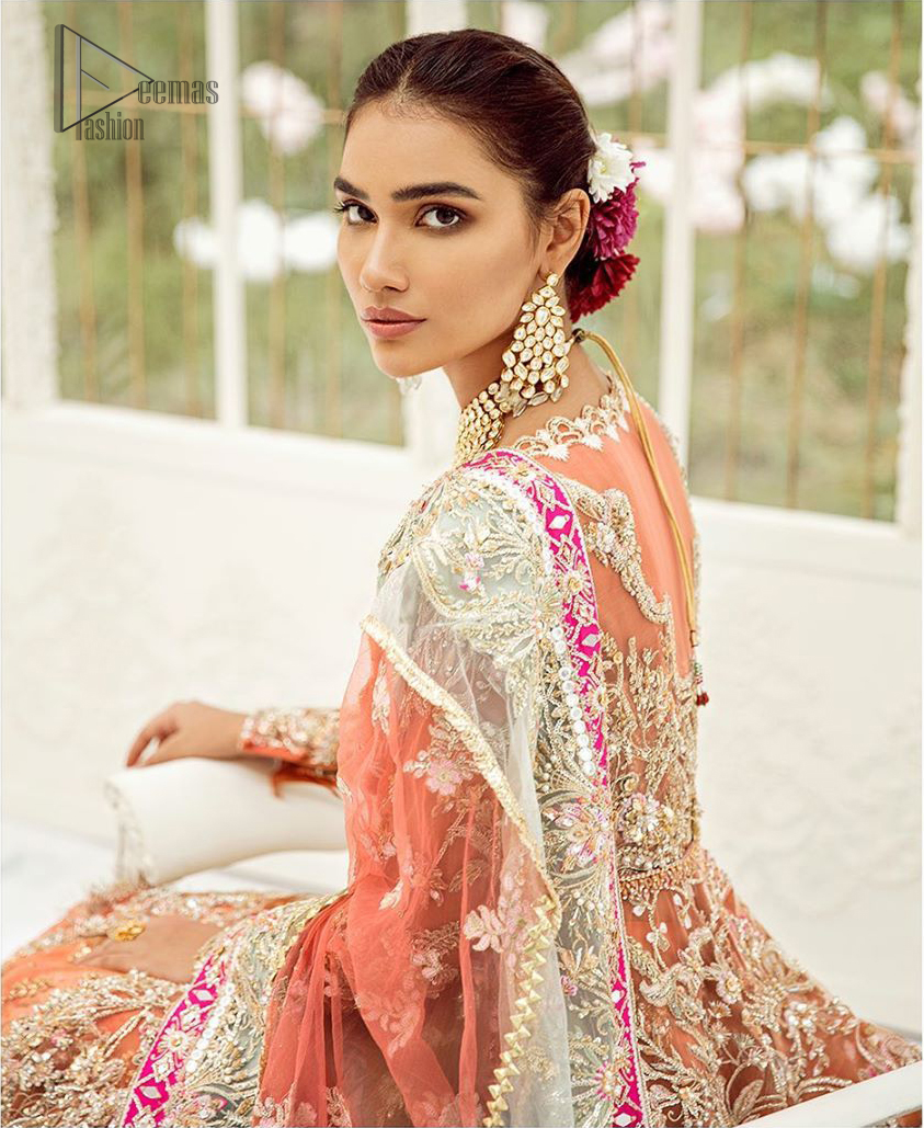 Captured in traditional silhouette, The bridal stands out due to its uniqueness and the perfect fusion of modern cut and traditional embroidery. This front open short frock is highlighted with kora, dabka, tilla, sequins and pearls. It comes with full embellished lehenga adorned with floral bunches, applique on the hemline and sequins spray all over it. It is coordinated with organza dupatta which is sprinkled with tiny floral motifs all over and a thick embellished border on all four sides with applique details.