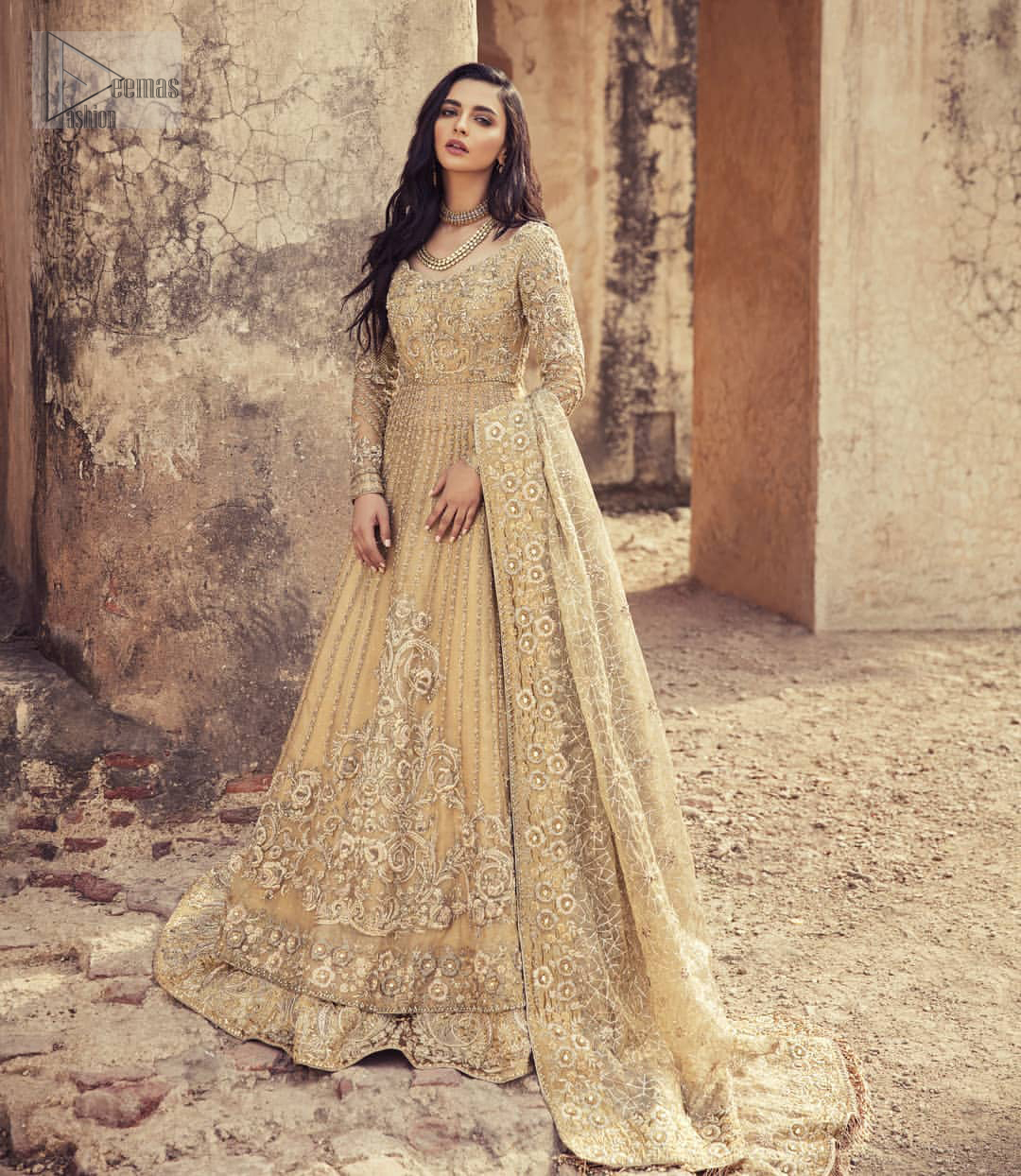 Captured in traditional silhouette, The bridal stands out due to its uniqueness and the perfect fusion of modern cut and traditional embroidery. It is highlighted with kora, dabka, tilla, sequins and pearls. Pishwas is enhanced with zardosi work on bodice, vertical lines and the daaman is emphasized with intricate zardosi details that gives perfect ending to this outfit. A handcrafted pale gold lehenga finished with thick embellished borders completes the look. The outfit is coordinated with chiffon dupatta with hand embroidered borders on all four sides and geometric patterns on the ground.