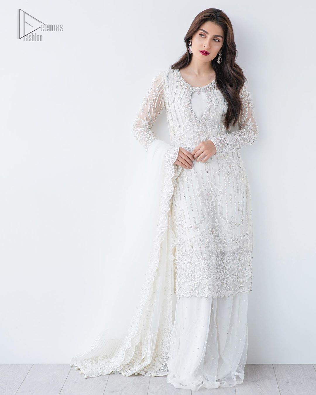 This is an ensemble that deserves to be flaunted. The ivory white shirt is an example of remarkable handiwork. With a lot of attention to detail, the intricate sequencing using glass beading and threads makes the shirt look like nothing but a dream. Furthermore the shirt is enhanced with thick embellished scalloped hemline. Sharara is magnificently decorated with scattered crystals all over. Beautifully paired it up with ivory white dupatta having four sided scalloped border.