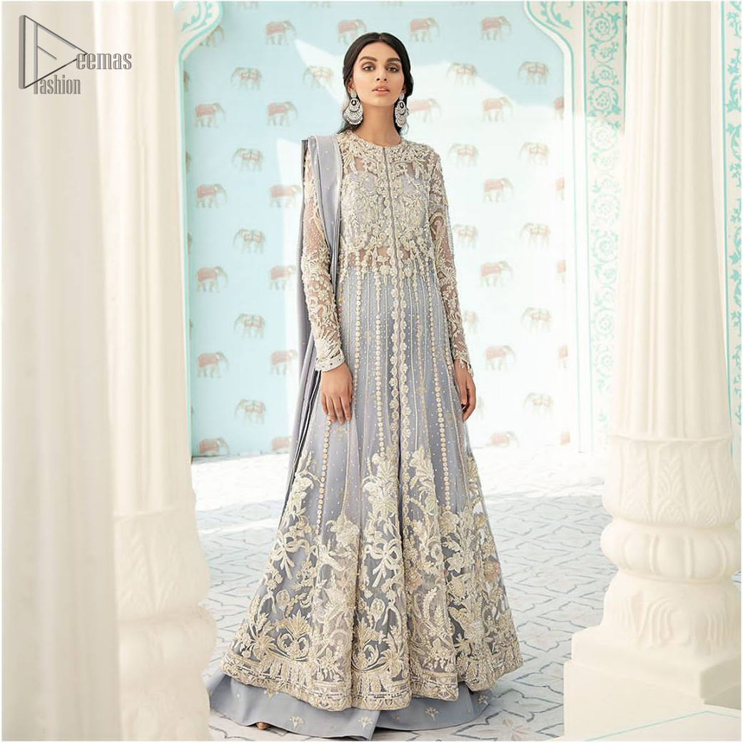 You are all set to make a lasting impact with the divine royalty of this dress. This artisan piece includes intricate hand-embellishment. This technique gives this garments a unique look, and helps to sustain a traditional craft carried out by skilled artisans. This multiple panels front open maxi is ornamented by light gold zardozi work with beautiful embellished motifs around the hem and vertically worked gold lines. It comprises with raw silk sharara adorned with tiny floral motifs and dupatta is decorated with sequins spray all over.