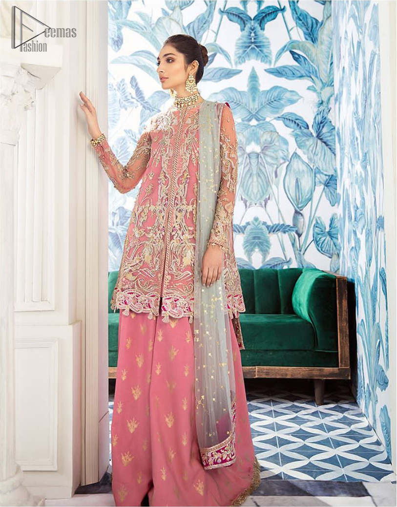 Let the crowd stare and make it worth their while when you walk wearing this outfit. A perfect ensemble for this festive season with divine detailing of thread embroidery, color balance and well-crafted applique hemline. The front open frock is fully embellished with floral embroidery done with light golden zardozi work and thread embroidery. It comprises with pink self fabric sharara and mint green dupatta, adorned with sequins spray on the ground and embellished pink applique pallu. You would definitely want to wear this for your next occasion.