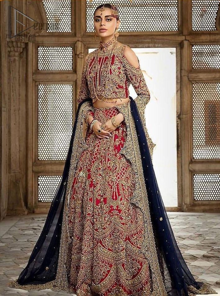 A breathtaking red traditional lehenga paired with a detailed blouse, equally alluring make for an ensemble which is comfortably chic. The blouse is done with golden and antique shaded embroidery and finishing with tassels. Blouse having cold shoulder full sleeves. The lehenga is enhancing with the art of classical heritage showcasing the craftsmanship of kora, dabka, tilla, kundan and sequins detailed, artistically embellished to give a beautiful rhythm to the outfit. It comprises with navy blue dupatta sprinkled with sequins and four sided scalloped border. This is an ensemble that is sure to invite compliments galore.