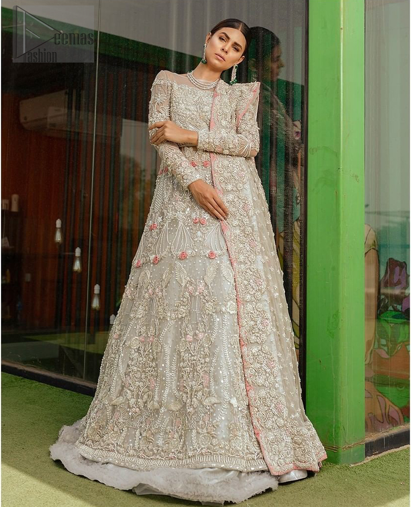 This garnet ensemble is sure to make you look like glamorous royalty with immaculate work covering every inch of the maxi. With a flowing train, this is an ensemble that deserves to be flaunted. The maxi is crafted artfully with silver zardozi work and multiple color thread embroidery. The bodice is heavily decorated with silver kora, dabka and tilla work. Furthermore, scattered sequins all over to give it a perfect look. Balance the look with light gray lehenga adorned with frilled bottom. Dupatta is decorated with vintage floral on pallus and finished with embroidered border on four sides which makes this outfit more beautiful.