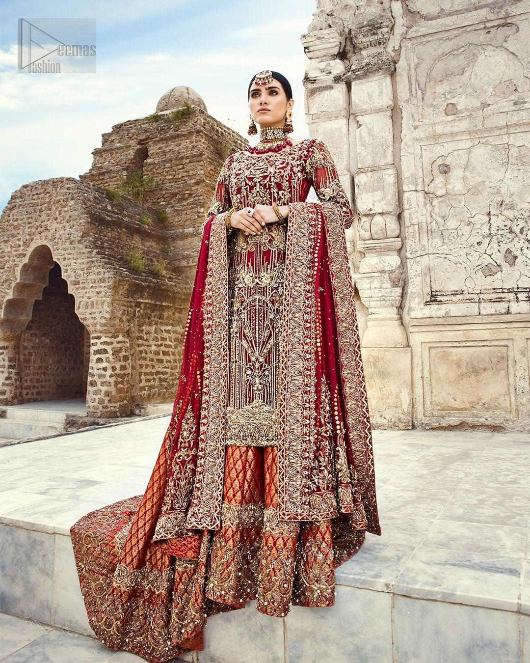 You are all set to make a lasting impact with the divine royalty of this dress. This beautiful dress comes with a maroon back train lehenga with beautiful embellishment around the hem. The shirt is adoned with golden zardozi work around the neckline and vertically worked gold lines and it finished with a thick embellished border. The sleeves are embellished with motifs all over along with a thick embroidered border. The dupatta incorporates beautifully designed borders on all four sides, focusing on the heavily embellished pallu borders to give it a perfect maharani look.