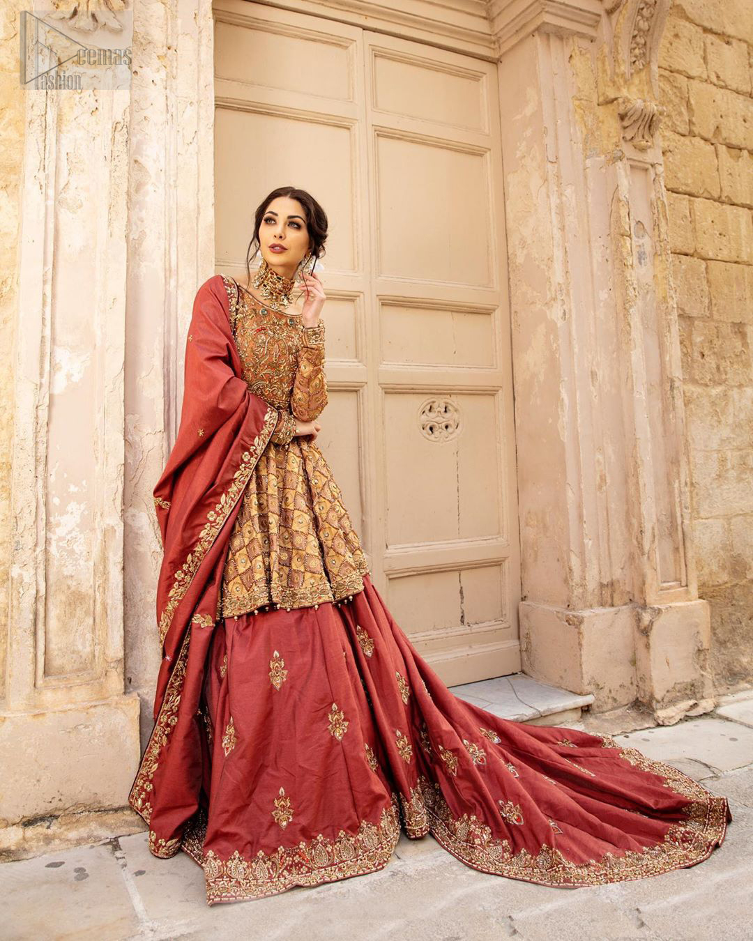 Chic and sophisticated perfectly describe this simply stunning wedding dress. This artisan piece includes intricate hand embellishment. This technique gives our garments a unique look, and helps to sustain a traditional craft carried out by skilled artisans across Asia. The short frock is fully embellished with zardozi work in the shades of golden and silver on tea rose canvas. Finished with dangling pearls on hemline. Compliment the look with coral back train lehenga exaggerated with embellished bottom and sprinkled floral bunches. The coral raw silk dupatta is emphasized with intricate embroidered borders.