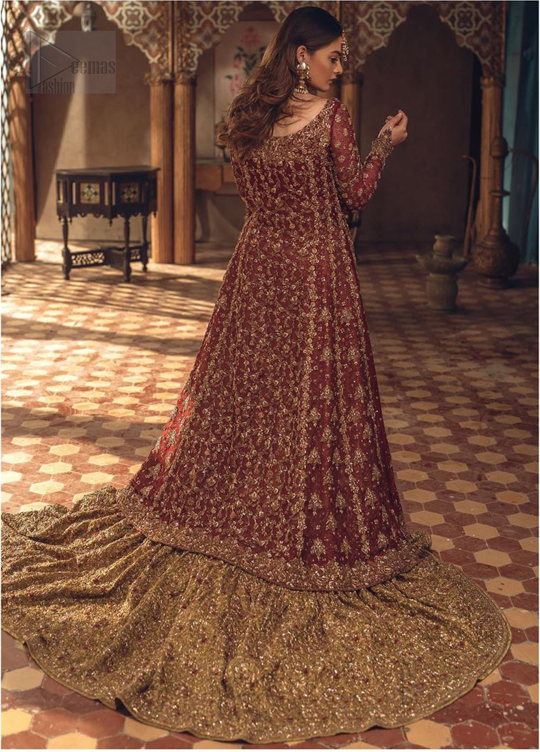 This wedding season, create a blissful aura with the treasure of love and elegance. An artistic vision of classic style and luxurious detailing, transpire into a truly romantic and iconic bridal for your big day. The front open floor length maxi is adorned with unique geometric patterns around the neckline and rest of the maxi is ornamented with floral embroidery. The kora, dabka, tilla and pearls embroidery is done in the shade of tan. Compliment the look with wide flared lehenga. The combination ofgolden with maroon is absolutely breathetaking. The dupatta incorporates beautifully designed borders on all four sides and sprinkled sequins to give it a perfect maharani look.