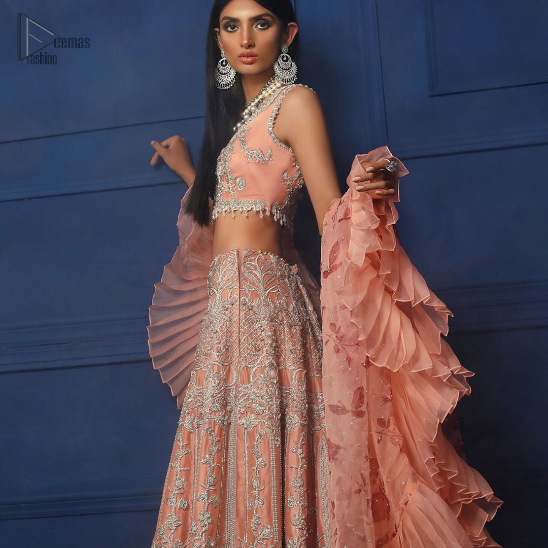 Crafted with love. This outfit is classically designed to make your memorable day beautiful as it should be. The peachy blouse is emphasized with intricate embroidery, handcrafted bootis adorned with silver embellishment finished with dangling pearls all around the edges. Compliment the look with flared lehenga which is decorated with silver kora, dabka, tilla and pearls work. Excellence of craftsmanship is evident with intricate detailing that features the use of zardozi work. The look is complete with organza dupatta finishing with frilled border.