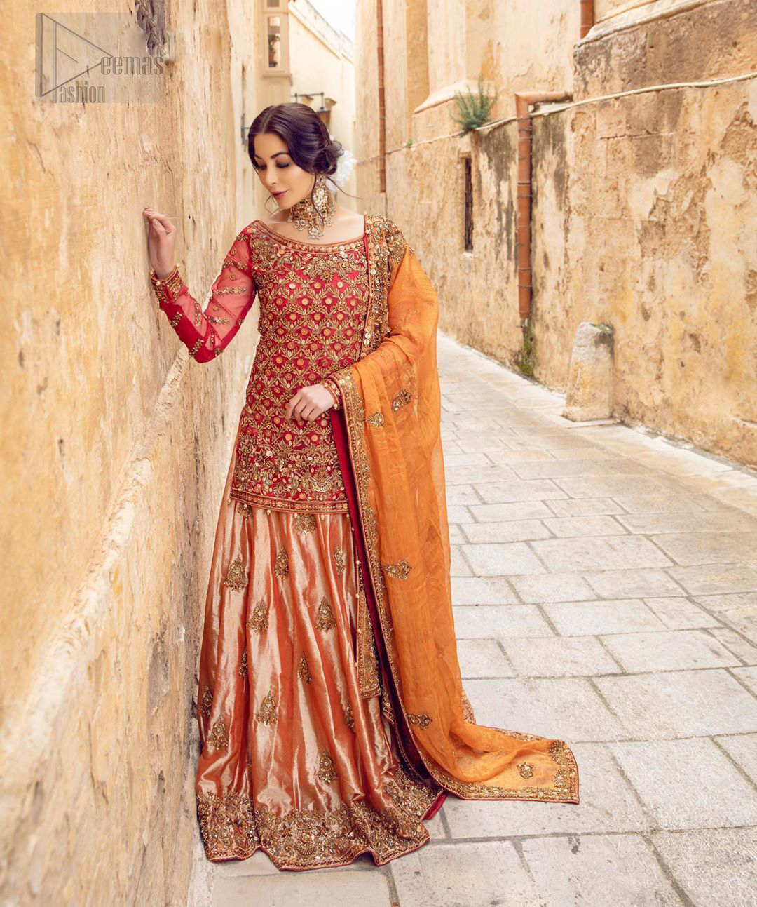 Make your big day more beautiful with our excessively embroidered back train lehenga shirt featuring delicately embellished neckline along with geometric patterns highlighted in antique shaded embroidery detailing and intricately embroidered borders that gives perfect ending to this outfit. Pair it up with a breathtaking back train lehenga with scattered motifs on the ground and embellished hemline. The orange organza dupatta with floral motifs and finishing all around the edges makes the look complete. The combination of orange with red is absolutely breathetaking.