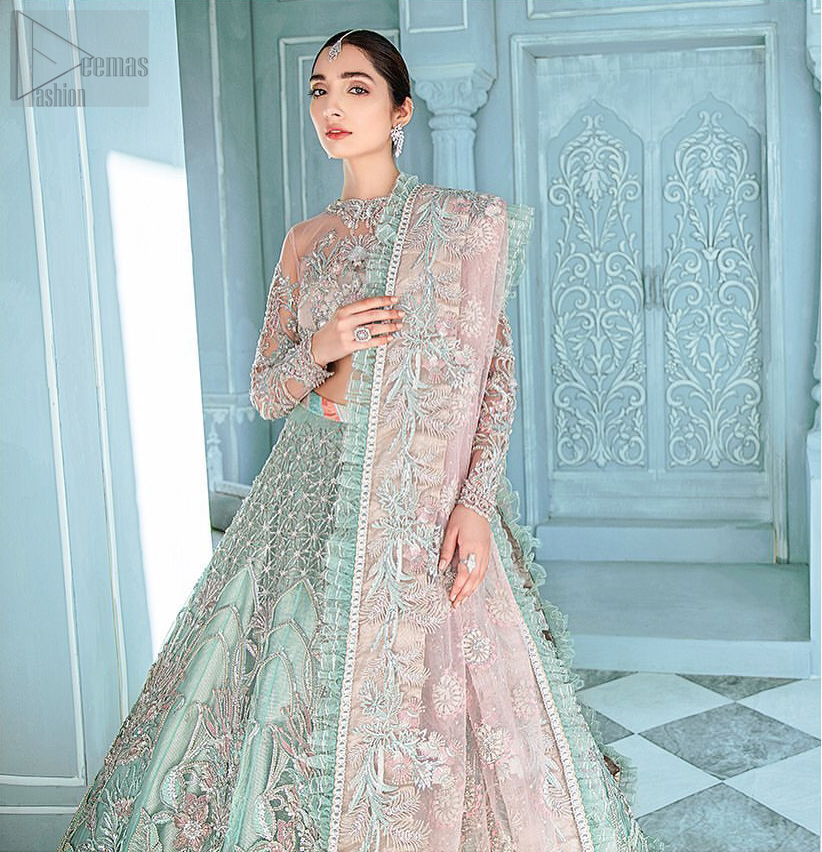 A enchanting amalgamation. This fairytale ensemble is everything that you need to impress everyone. The fusion of rich fabrics intricately designed with floral powdery hue. Precious uncut stones are threaded together with silver zardozi on pastel color palette to give it an enchantingly exquisite look. The illusion neckline blouse is laden with silver kora, dabka details and pair it up with a beautiful lehenga. The lehenga is adorned with colorful chatta patti waist belt and a captivating geometric jaal finished with scattered floral motifs and scalloped hemline. Finish the look with pink dupatta focusing on heavily embellished borders on all four sides to give it a perfect maharani look.