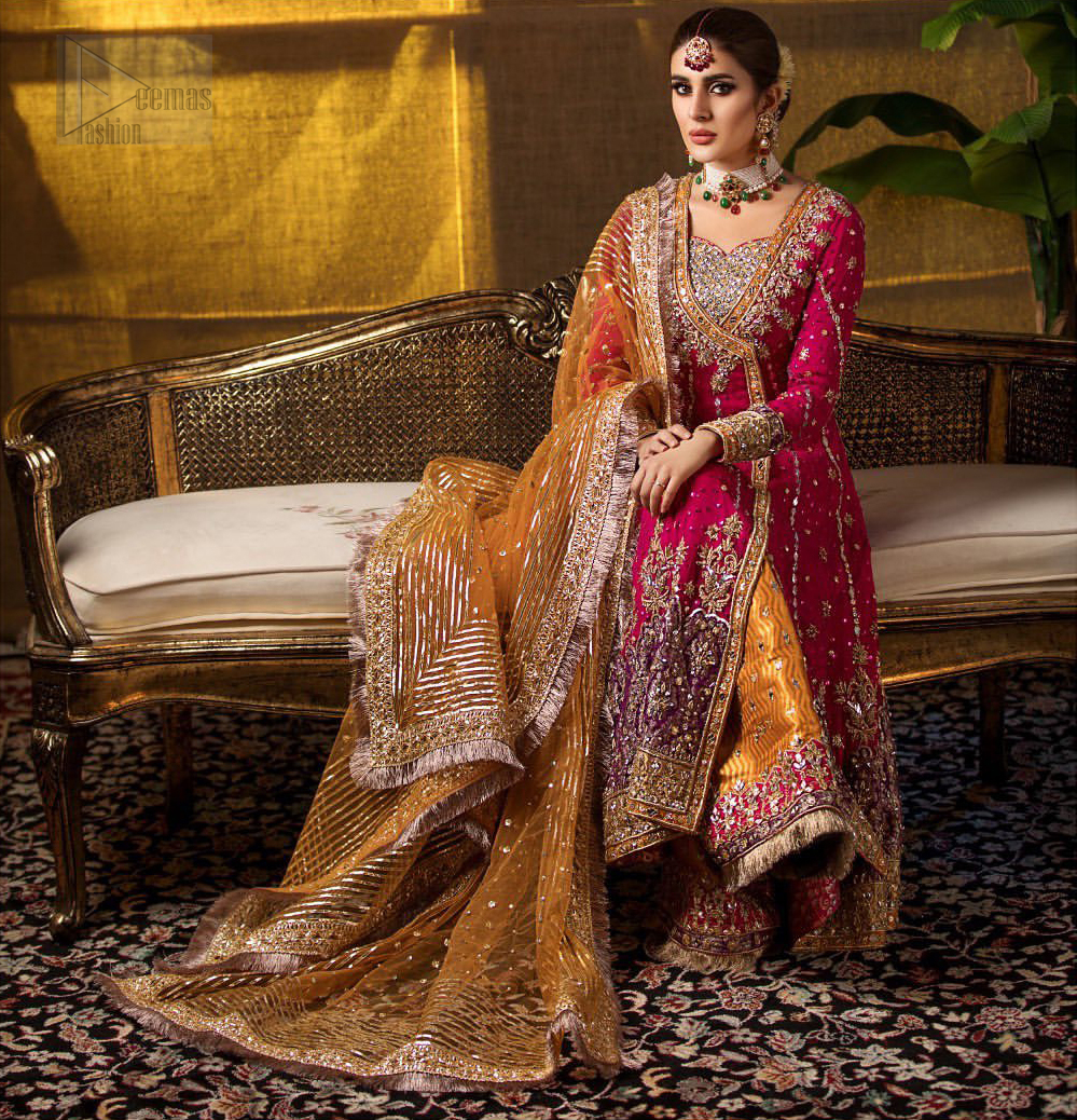 Impeccably on trend. The chic yet elegant front open angrakha style frock is decorated with vertical embroidered lines, embellished neckline and floral bunches. Borders are even more enhanced with rust applique details done with golden and light golden zardozi work. It comes with brocade rust sharara exaggerated with embroidered pink applique on the bottom. Elegance is personified when it gets paired up with rust dupatta decorated with four sided kiran lace and zardozi work on all four sides.