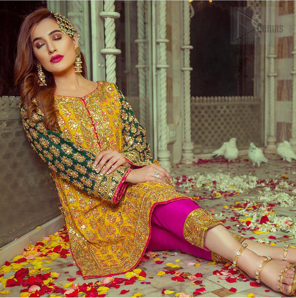 Embrace the season of festivities with this beautiful dress. This beautiful mehndi dress comes with a pink capri pants with beautiful embellished applique around the bottom and the shirt is designed with vertically worked gold lines and it finished with a thick appliqued embellished border. The shirt looks more whimsical when it comes with embellished green sleeves with golden zardozi work. Balance the look with yellow organza dupatta scattered with sequins on the ground.