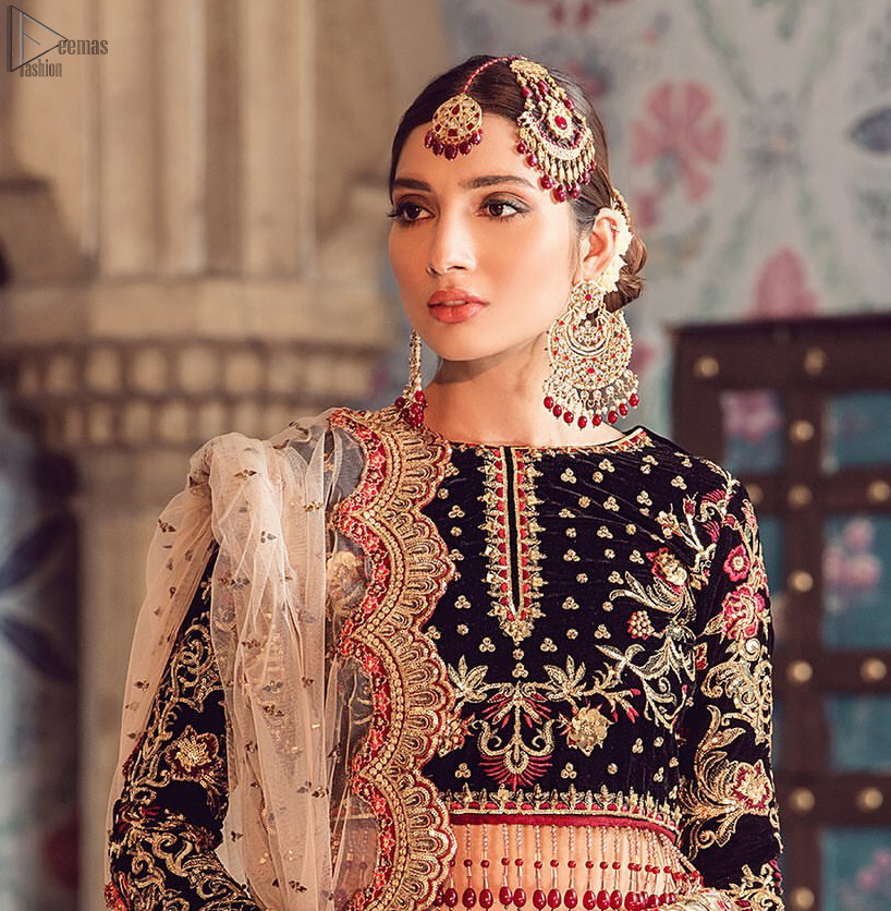 The new season is all about making a statement. Captured in traditional silhouette, The bridal stands out due to its uniqueness and the perfect fusion of modern cut and traditional embroidery. Black velvet blouse is beautifully decorated with multiple colour embroidery and finished with tassels. It comes with full embellished velvet lehenga adorned with applique all around the edges and motifs all over it. This outfit is coordinated with beige net dupatta which is sprinkled with sequins all over it. It is further furnished with a four-sided scalloped border.